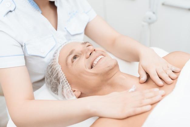 Le médecin applique une crème de soin sur la poitrine et les épaules de l'homme. Photo Premium