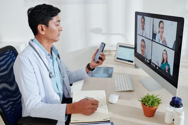Médecin Asiatique D'âge Moyen Sérieux Ayant Une Conférence En Ligne Avec Des Collègues Et Prenant Des Notes Dans Le Planificateur Photo Premium
