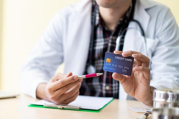 Médecin asiatique montrant une carte de crédit au patient. concept de soins de santé et d'assurance. Photo Premium