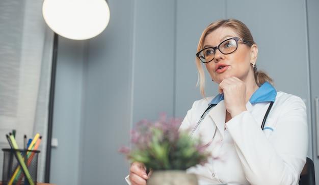 Médecin Blonde Senior Avec Des Outils Médicaux Parle Au Patient Lors D'une Consultation Photo Premium