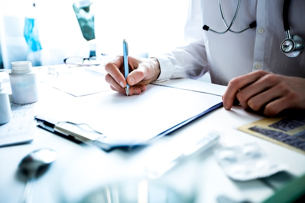 Le médecin en blouse de laboratoire écrit une ordonnance sur une feuille de papier, assis à la table de la clinique. Photo Premium