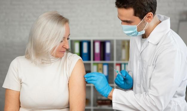 Médecin Coup Moyen Administrant Le Vaccin Photo gratuit