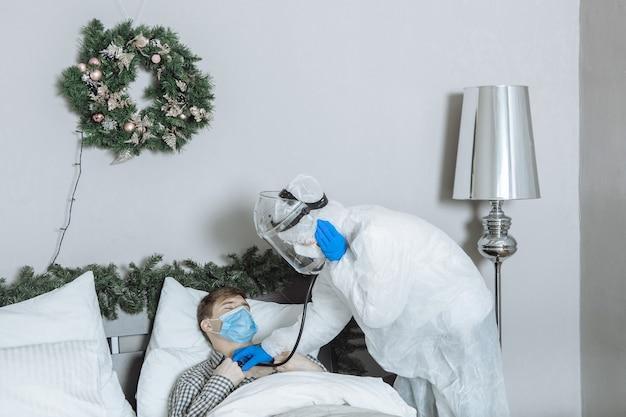 Médecin Dans Une Combinaison De Protection En Ppe écoute Un Patient Avec Un Stéthoscope à La Maison Avant Le Nouvel An Et Noël Photo Premium