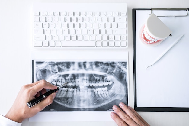 Médecin ou dentiste travaillant avec le film radiographique, le modèle et l'équipement utilisés pour le traitement Photo Premium