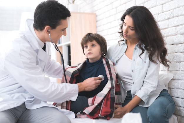 Un médecin écoute le cœur d'un garçon malade dans un stéthoscope. Photo Premium