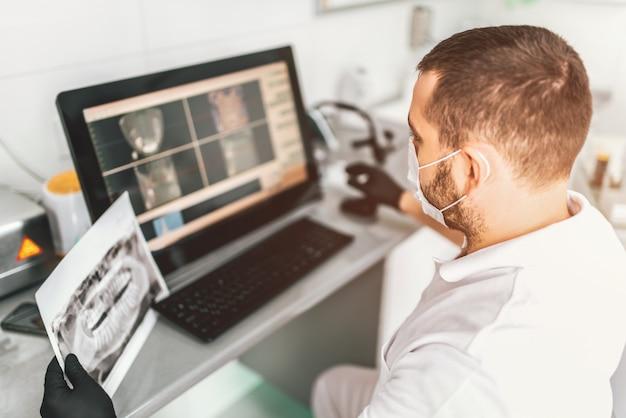 Médecin effectuant un examen radiographique et choisissant un traitement en clinique dentaire Photo Premium