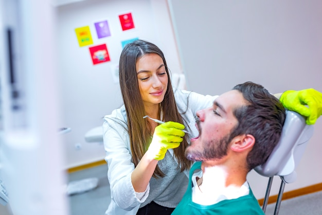 Médecin effectuant un traitement dentaire sur les dents de l'homme dans son fauteuil. Photo Premium