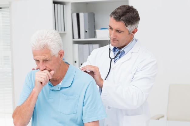 Médecin examinant toussant un patient senior Photo Premium
