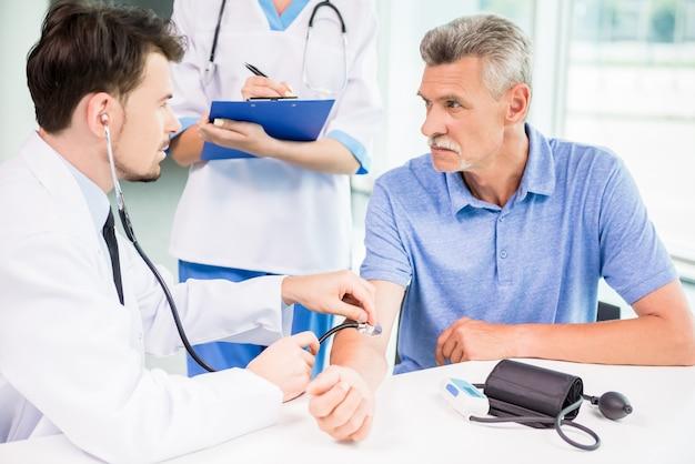 Médecin examine son patient mature avec un stéthoscope. Photo Premium
