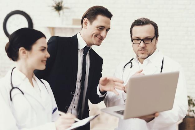 Médecin expérimenté montre sur les résultats de l'ordinateur portable. Photo Premium