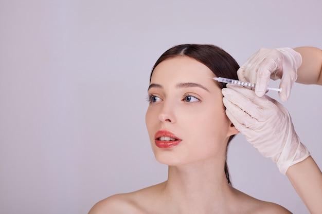 Médecin Fait Une Injection Dans Le Front D'une Jeune Femme Photo Premium