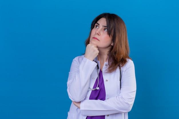 Médecin De Femme D'âge Moyen Portant Un Manteau Blanc Et Avec Stéthoscope Debout Avec La Main Sur Le Menton à La Recherche D'expression Pensive Sur Fond Bleu Photo gratuit