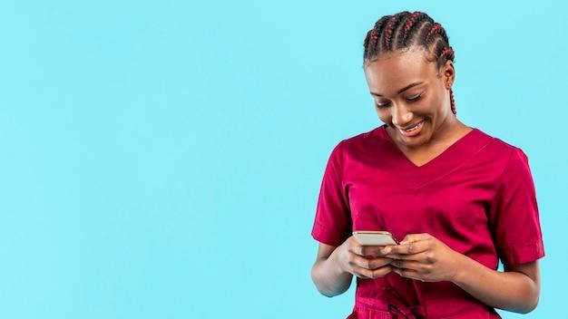 Médecin Femme Regardant Son Téléphone Photo gratuit