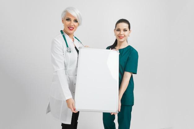 Médecin et infirmière détenant un tableau magnétique vide isolé sur fond blanc Photo Premium