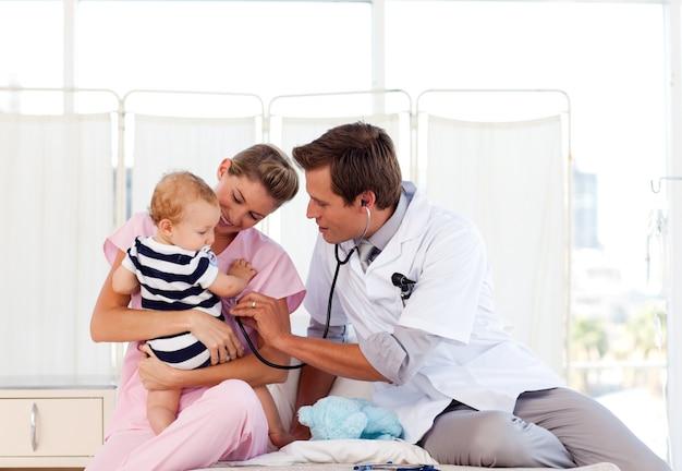 Médecin et infirmière jouant avec un bébé Photo Premium