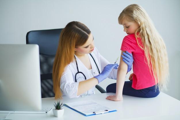 Médecin injectant la vaccination dans le bras petite fille enfant, concept sain et médical Photo Premium