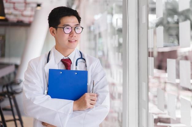 Médecin intelligent asiatique debout bras croisés et tenant un fichier de document bleu. Photo Premium