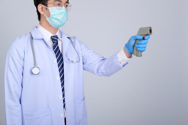 Médecin Médecin Praticien Mesurant La Température Corporelle Avec Pistolet Thermomètre Frontal Infrarouge Photo Premium