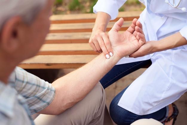 Le médecin mesure le pouls du patient assis sur un banc Photo Premium