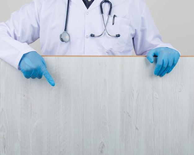 Médecin Montrant Une Planche De Bois En Blouse Blanche Et Gants Photo gratuit