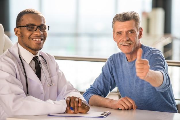 Médecin et patient souriant et bravo. Photo Premium