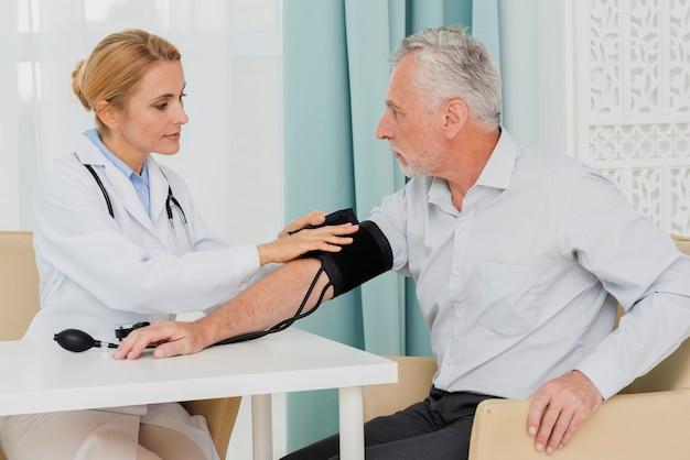 Médecin plaçant le brassard de tensiomètre Photo gratuit
