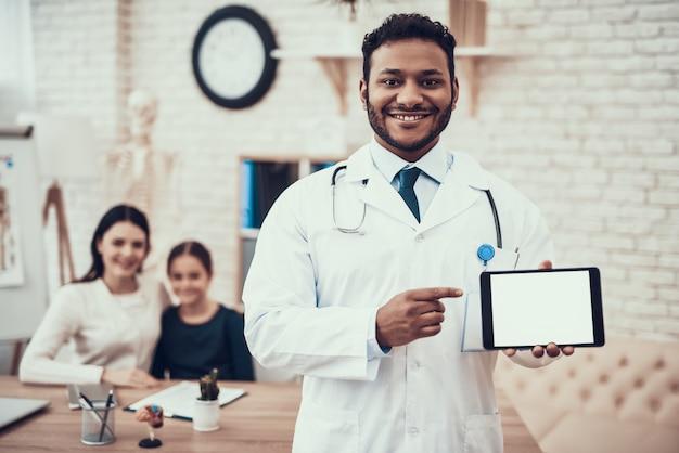 Médecin pose avec tablette avec mère et fille. Photo Premium