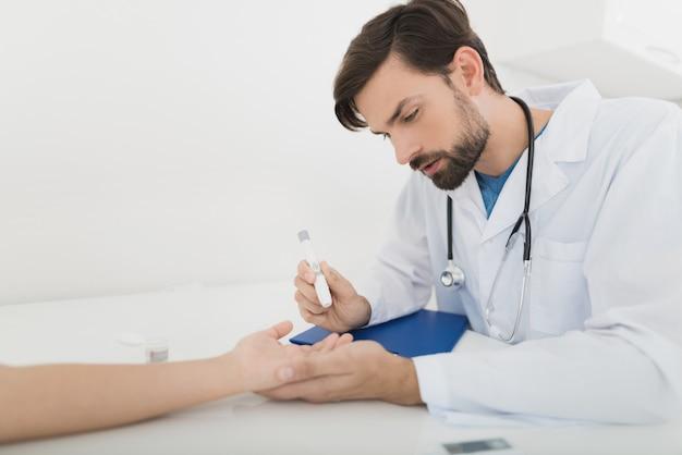 Le médecin prélève un échantillon de sang sur un garçon pour vérifier s'il contient du sucre. Photo Premium