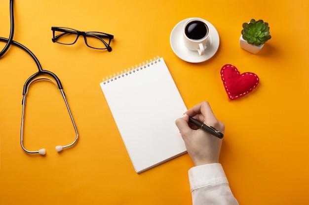 Médecin professionnel écrivant des dossiers médicaux dans un cahier avec stéthoscope, tasse à café et coeur Photo Premium