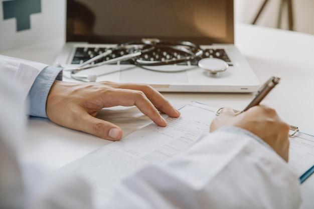 Médecin Remplissant Un Formulaire Médical Assis Au Bureau Du Bureau De L'hôpital. Médecin Au Travail. Photo Premium