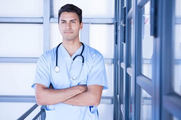 Médecin de sexe masculin sérieux debout avec les bras croisés à l'hôpital Photo Premium