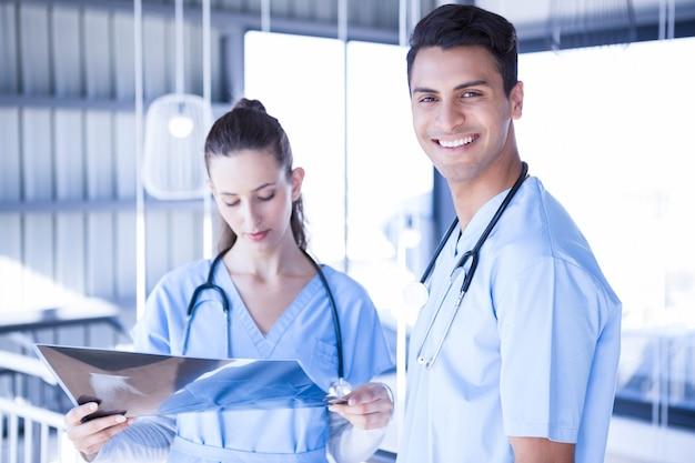 Médecin souriant examinant un rapport de rayons de rayons x avec son collègue à l'hôpital Photo Premium