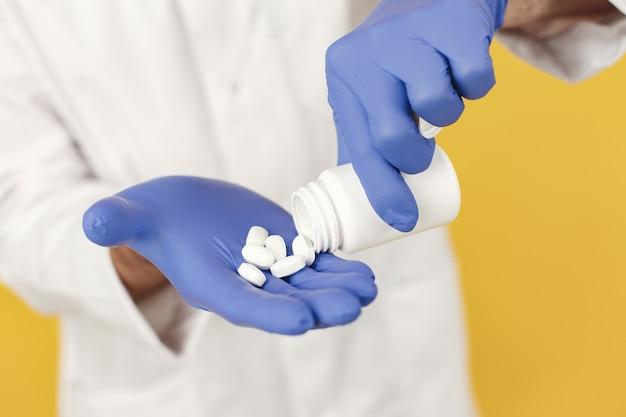 Médecin Souriant Avec Des Pilules. Isolé. Homme Dans Des Gants Bleus. Photo gratuit