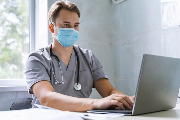 Médecin Avec Stéthoscope Et Masque Médical Travaillant Sur Ordinateur Portable Photo gratuit
