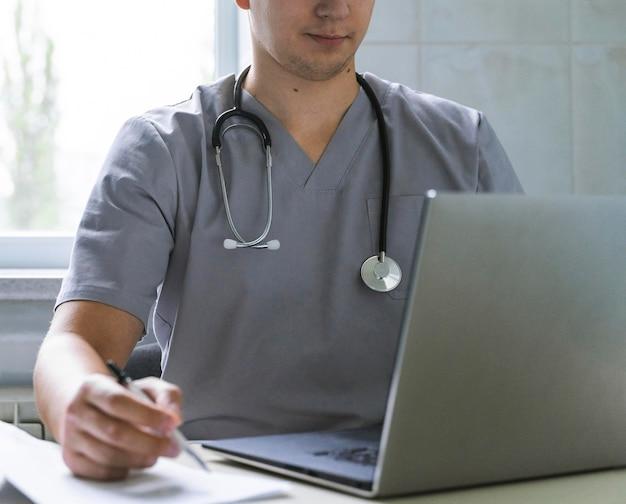 Médecin Avec Stéthoscope Travaillant Sur Ordinateur Portable Photo gratuit