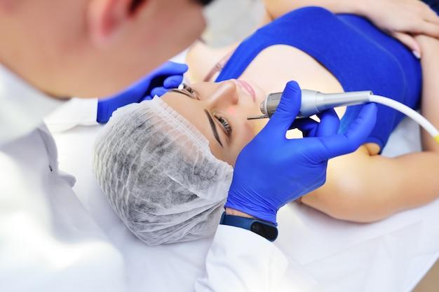 Le médecin supprime les taupes de pigmentation ou les verrues au néodyme du patient. Photo Premium