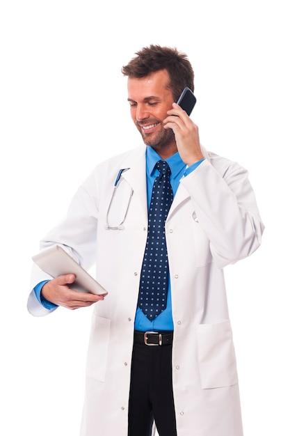 Médecin Avec Téléphone Portable Vérifiant Quelque Chose Sur Une Tablette Numérique Photo gratuit