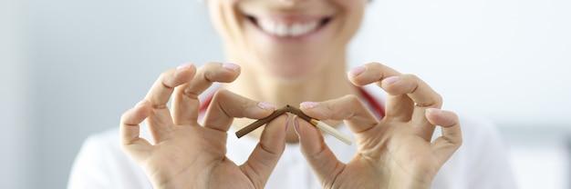 Médecin Tenant La Cigarette Dans Ses Mains Et Le Casser En Gros Plan De La Clinique. Dommage Du Concept De Fumer Photo Premium