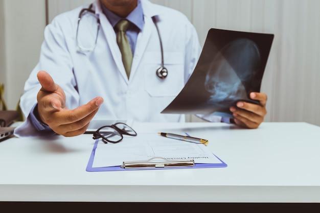 Un médecin tenant un film radiographique et consulte un patient au bureau. Photo Premium