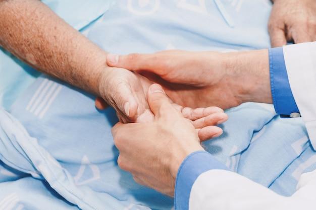 Médecin tenant la main de la personne âgée avec soin à l'hôpital. soins de santé et médecine Photo Premium