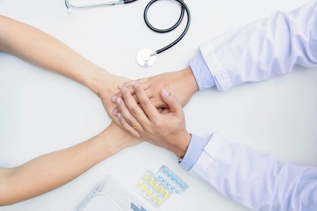Le Médecin Tient Les Mains Du Patient. Il Lui Donne De L'espoir Et Le Soutient Photo Premium