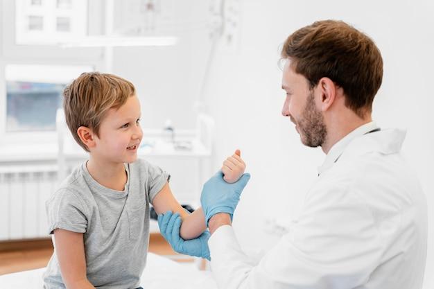 Médecin De Tir Moyen Tenant Le Bras De L'enfant Photo gratuit