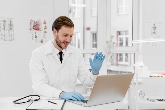 Médecin De Tir Moyen Travaillant Sur Ordinateur Portable Photo gratuit