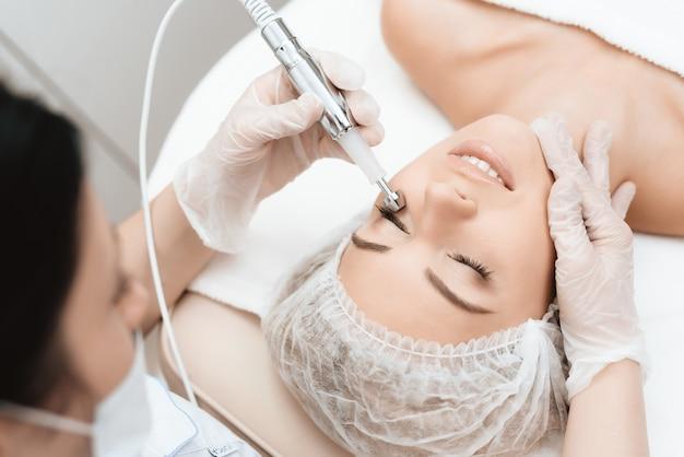 Le médecin traite le visage des filles avec un photoépilateur Photo Premium