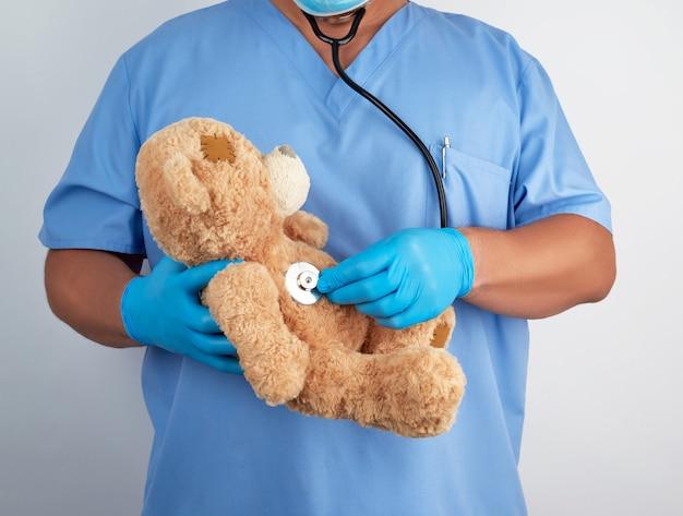 Médecin En Uniforme Bleu Et Gants En Latex Blanc Tenant Un Ours En Peluche Brun, Photo Premium