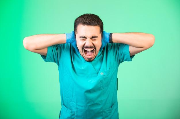 Médecin En Uniforme Et Masque à La Main Ayant Un Choc émotionnel. Photo gratuit