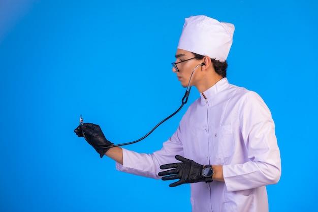Médecin En Uniforme Médical Blanc Contrôle Avec Stéthoscope à La Main Des Masques Sur Fond Bleu Photo gratuit
