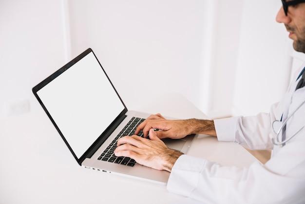 Médecin utilisant un ordinateur portable avec un écran blanc Photo gratuit