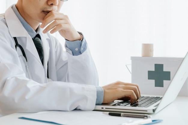 Un médecin utilise un ordinateur, effectue des recherches et des analyses, analyse des maladies et enregistre les informations relatives au patient, Photo Premium