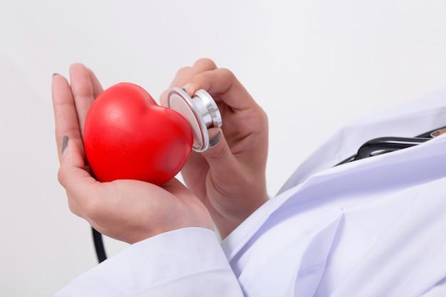 Médecin vérifiant le coeur rouge avec la ligne ecg et stéthoscope Photo Premium